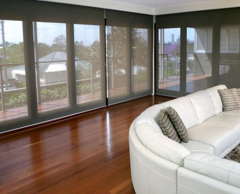 Lounge chair in living room in front of roller blinds | Featured image for curtains and blinds - U Blinds Australia Home Page.