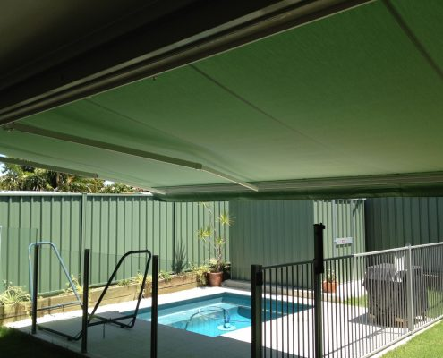 Green Folding arm awnings covering a pool | Ublinds