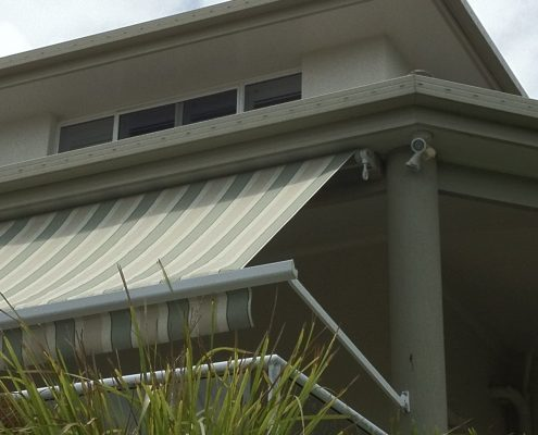 yellow and brown stripe pivot arm awnings | Ublinds